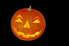 Horizontal pumpkin with scary face. Candlelit glowing pumpkin lantern isolated on black stock photos