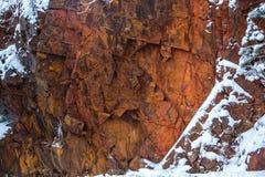 Horizontal Red Granite. Wisconsin red granite rock with December snow Royalty Free Stock Image