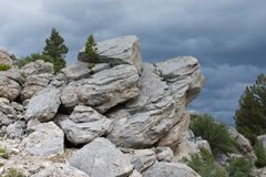 Horizontal Rock Formation. A rock formation jutting out of the ground with pine trees and shrubs and dark gray clouds above. Photographed in natural light in Royalty Free Stock Photography