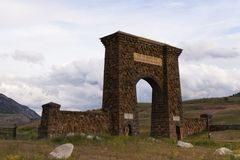 Horizontal Roosevelt Arch from Gardiner. The Roosevelt Arch at the entranace of Yellowstone National Park with mountains and foothills in the background and Royalty Free Stock Photo