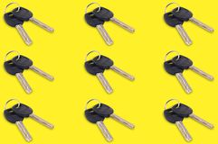 Horizontal rows of metal shiny keys with black plastic or rubber handle attached of keyring for door or car on yellow background. Seamless pattern stock photography