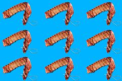 Horizontal rows of smoked ribs of pork on blue background. Seamless pattern stock photography