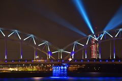 Bright illuminated Railroad Bridge. Latvian Television building bright illuminated in red and white. Blue spot beams projected fro stock photos