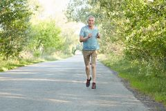 Horizontal shot of active senior male runs on asphalt very quickly, dressed in spotswear, goes in for sport regularly, breathes fr. Esh air in countryside Stock Photography