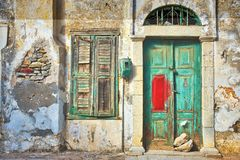 Horizontal shot of an ancient green wooden door and a window on an old yellow wall in Greece
