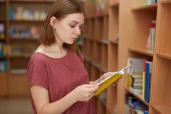Horizontal shot of attentive female reader with short hairstyle, stands near shelfs with books in library, reads review before royalty free stock photography
