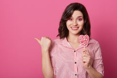 Horizontal shot of attractive smiling woman with pleased expression, points with thumb, holds candy in form of heart, isolated royalty free stock images