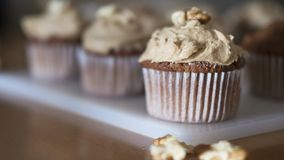 Plenty of coffee and walnut homemade cupcakes with coffee icing with selective focus. Horizontal shot of baked goods, just taken out of the oven, positioned on a Royalty Free Stock Photography