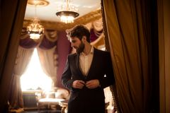 Horizontal shot of bearded male entrepreneur dressed in formal suit, stands in royal room with luxury curtains and. Furniture, being very rich, looks Royalty Free Stock Images