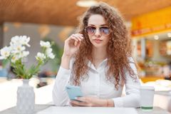 Horizontal shot of beautiful curly woman with confident look, wears sunglasses and white blouse, holds modern cell phone, reads ne Stock Photography