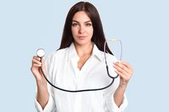 Horizontal shot of beautiful professional female therapist with stethoscope, dressed in white gown, going to examine patient, has royalty free stock photography