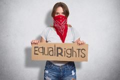 Horizontal shot of beautiful young female belong to feminist move, wears red bandana on face, holds plate with inscription Equal r. Ights, demonstrates womens royalty free stock photography