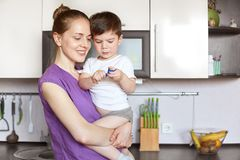Horizontal shot of beautiful young smiling female holds her son on hands, have positive expression, stand against kitchen interior. With modern furniture, going Stock Images