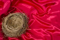 Empty Bird`s Nest on a Beautiful Red Satin Background. Horizontal shot of a bird`s nest in the lower left hand corner of the shot on a beautiful red satin Stock Images