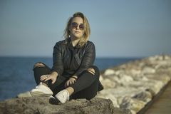 Blonde girl sitting on the rocks 3 royalty free stock photography