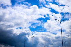 A horizontal shot of bright blue sky with white clouds. Photo made in the city with light pillars in dynamics and some rainy clouds Royalty Free Stock Photos