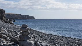 Solitary pebble beach with one rock cairn in a sunny morning, at Playa de San Juan, Tenerife, Canary Islands, Spain. Horizontal shot of bright morning on Playa Royalty Free Stock Images