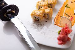Horizontal shot of California sushi rolls with a sauce and lemon on a white plate by a sword