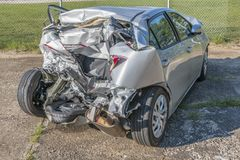 Demolished Car From the Back. Horizontal shot of a car demolished by a wreck at an angle from the back Royalty Free Stock Image