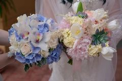 Caucasian women`s hands holding two stylish bridal or bridesmaids bouquets stock images