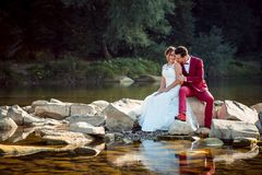 Horizontal shot of cheerful charming newlywed couple laughing and sitting on the snotes near the beautiful river. Horizontal shot of cheerful charming newlywed Royalty Free Stock Photo