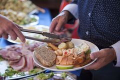 Senior male individual holding a plate with a selection of cold bits, bread and salad and being served a slice of meat. Horizontal shot of a chef handing a slice Royalty Free Stock Image