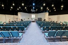 Empty Church Auditorium. Horizontal shot of a church auditorium from the back facing toward the stage looking down the center aisle royalty free stock image