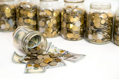 Horizontal shot of coins spilling from coin jar. Coins Spilled From Coin Jarn Stock Photography