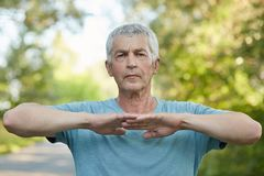 Horizontal shot of confident male pensioner has outdoor workout, warms up before jogging, stretches hands, spends leisure time in Stock Image