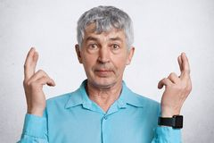 Horizontal shot of confident wrinkled grey haired attractive male wears formal blue shirt and smart watch, crosses fingers, has gr. Eat wish to achieve something Royalty Free Stock Photo
