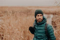 Horizontal shot of contemplative good looking man has stubble, wears hat, jacket and gloves, stands near wheat field background royalty free stock images