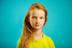 Horizontal shot of cute children girl with sincere look of kindness and honesty, has red hair, beautiful freckles, wears. Yellow t-shirt, portrait of child on royalty free stock photography