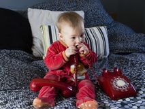 Cute fair baby girl sitting on bed sucking on vintage red telephone cord royalty free stock photos