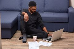 Horizontal shot of dark skinned young handsome male doing paper work at home, checking documents, drinking hot beverage, sitting stock images