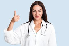 Horizontal shot of delighted female doctor keeps thumb raises, aprroves or gives agreement, wears white medical robe with stethosc royalty free stock photography