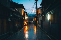 Horizontal shot of an empty pathway between houses in Japan during the nighttime while raining