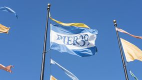 Flags with blue and white field and `Pier 39` words written on it, hoisted on a metal pole royalty free stock photography