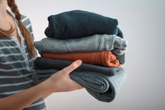 Horizontal shot of a Girl teenager with two braids holding a pile of clothes, isolated on gray background Stock Image