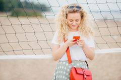 Horizontal shot of good looking female with curly hair, holds modern cell phone, texts messages to friend, stands near tennis net, royalty free stock images