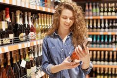 Horizontal shot of gorgeous attractive female with curly hair chooses alcoholic drink for party, reads label, wants something swee. T, likes wine and champagne royalty free stock photo