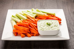 Horizontal shot of green dip with carrots and celery. Creamy radish kale green dip with carrots and celery horizontal shot Royalty Free Stock Photography