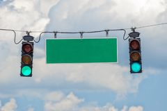 Green Traffic Light With Blank Street Sign. Horizontal shot of a green traffic light with a blank green sign.  Blue sky with clouds behind it Royalty Free Stock Photography