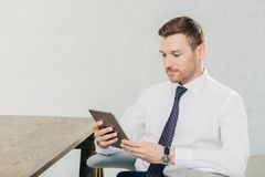 Horizontal shot of handsome young successful male fiinancier uses modern tablet computer, wears white shirt with tie, has break af. Ter work, sits at wooden Royalty Free Stock Photos