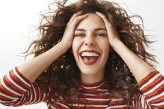 Horizontal shot of happy attractive feminine girlfriend with curly hair and red lipstick wearing striped sweater. Touching face gently while laughing, feeling royalty free stock image
