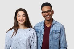 Horizontal shot of happy dark skinned young man and European woman, standing with positive expressions, dressed in casual clothes stock photos