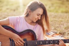 Horizontal shot of happy lovely female with positive smile plays guitar, learns new song, recreats oudoor in meadow, dressed in ca. Sual t shirt, has joyful stock photo
