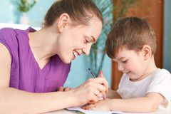 Horizontal shot of happy young smiling mother being glad to spend free time with her small son, draw something with great interest. Enjoy togetherness, have Stock Images