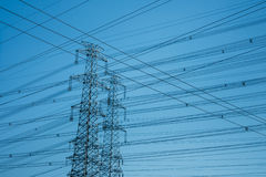 Horizontal shot of High-voltage towers silhouetted against blue. Sky Royalty Free Stock Photos