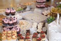 Delicious cupcakes with berries on a tiered cake-stand and a large assortment of sweets and cakes. Horizontal shot of indulgent delicious looking baked sweets Royalty Free Stock Photography