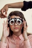 Horizontal shot of interested and curious caucasian girl on appointment with eye care specialist wearing phoropter while. Ophthalmologist checking her vision Royalty Free Stock Image
